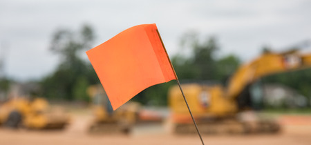 A bokeh close up shot of a warning flag at a construction site with heavy machinery equipment in the background.