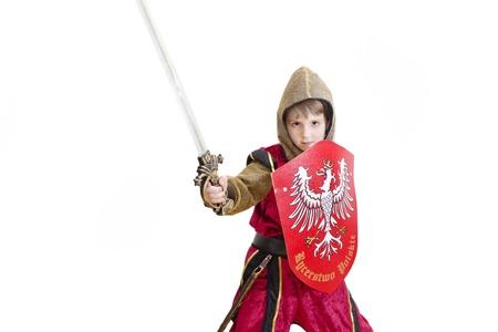 Jongen met carnaval kostuum. Kleine gevechten ridder met Poolse embleem op het schild.