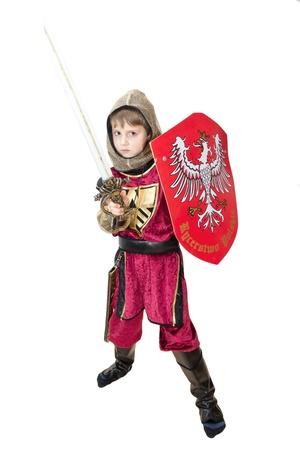 Jongen met carnaval kostuum. Kleine gevechten ridder met Poolse embleem op het schild. Stockfoto - 12877446