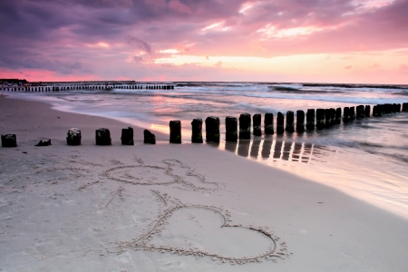Valentine s day on the beach  Beautiful sunset with symbol of love   photo