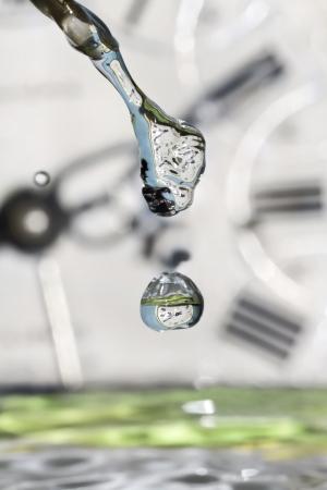 Druppels van de tijd. Spelen met water en klokken. Stockfoto