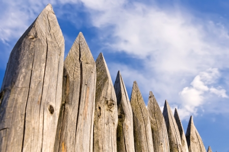 palisade: Wooden pales against cloudy sky.
