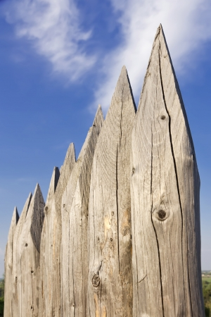 Wooden pales against cloudy sky.