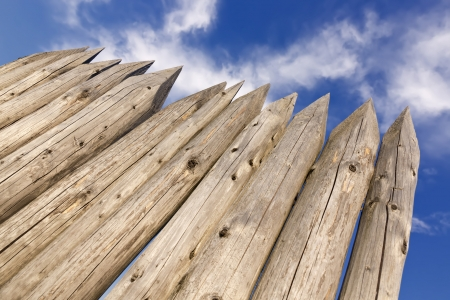 stockade: Wooden pales against cloudy sky.
