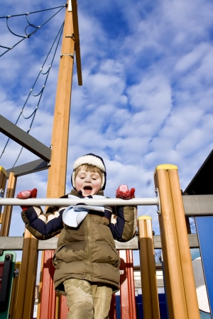 disobedient child: Boy with lollipop playing on a playground   Stock Photo