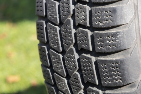retreading: Old car tire on green background