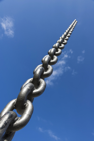 Black steel chain protruding in the sky. Blue sky and clouds.