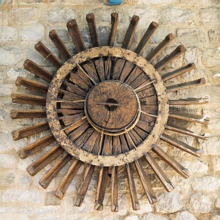 Old wooden wheel mill on the wall.