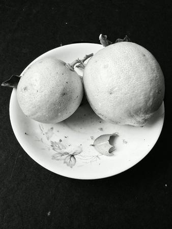 colour: Two ripe lemon in a white plate
