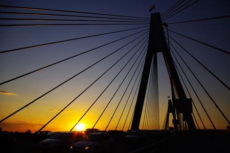The yellowish sunset and the busy Anzac Bridge, Sydney, Australia.