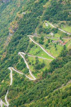 winding up: aerial tight view of a zig-zag winding road going up a steep slope near Geiranger, Norway with some traffics vertical Stock Photo