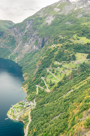 winding up: aerial tight view of a zig-zag winding road going up a steep slope near Geiranger, Norway with some traffics