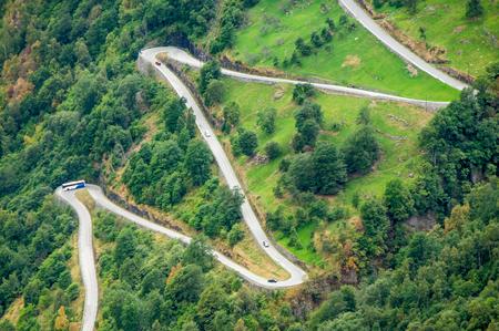 curvas: vista aérea estrecha de un camino en zig-zag sinuoso subiendo una empinada cuesta cerca de Geiranger, Noruega con algunos tráficos Foto de archivo