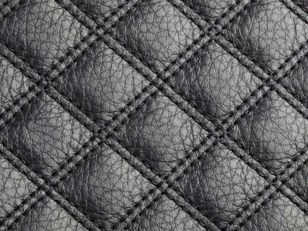 Genuine square stitched black cattle leather texture background. Macro photo