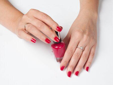 Closeup shot of woman`s hands with red manicure and a bottle of nail polish on a white background