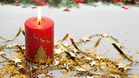 Christmas composition of the burning red Christmas candle, gold stars and garland on a light wooden surface with fir border