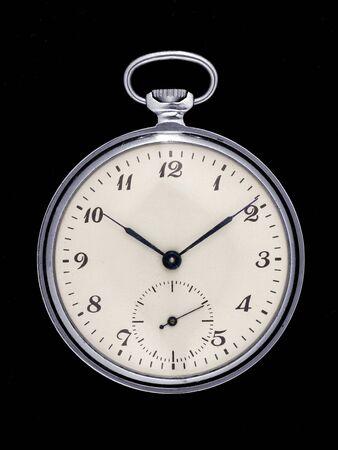Reloj de bolsillo retro aislado sobre fondo negro. Vista frontal