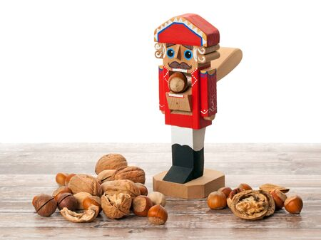 Nutcracker. Wooden Christmas toy with inshell and cracked nuts on wooden surface. With copy space