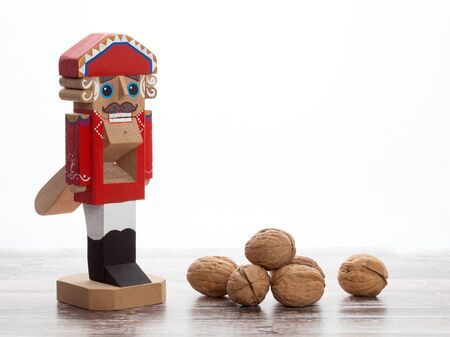 Nutcracker. Wooden Christmas toy with inshell walnuts on wooden surface. With copy space