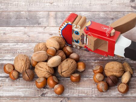 Nutcracker. Wooden Christmas toy with inshell nuts on wooden background. With copy space Stock Photo