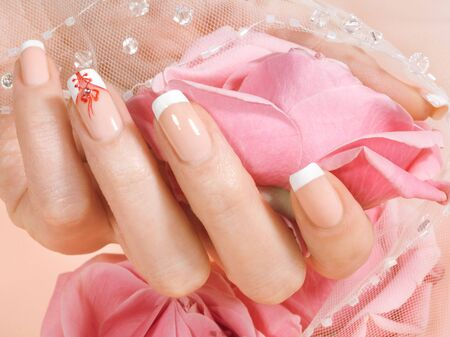 Closeup shot of woman`s hand with french manicure on pink floral background