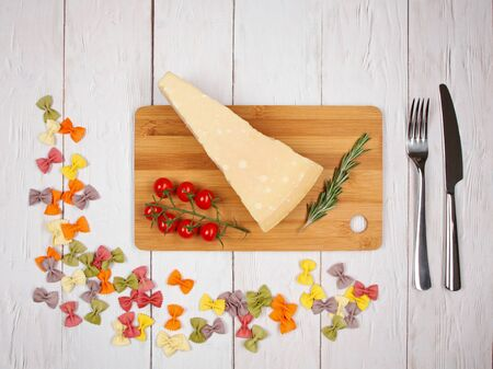 Dry Italian pasta farfalle with tomatoes, cheese, rosemary, fork and knife on light wooden background. With copy space