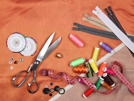 Set of tailoring tools and accessories on orange fabric. Top view, flat lay. With copy space
