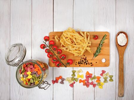 Dry Italian pasta fettuccini and farfalle with tomatoes, rosemary, mixture of peppers, glass jar, spoon with flour and board on light wooden background. Top view with copy space