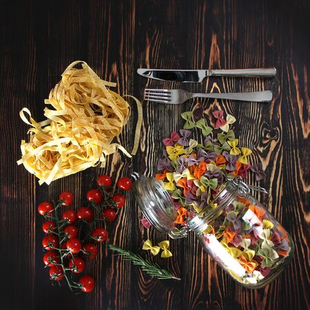 Dry colorful Italian pasta farfalle or bows and fettuccini with glass jar, tomatoes, rosemary, fork and knife on dark wooden background. With copy space Stockfoto