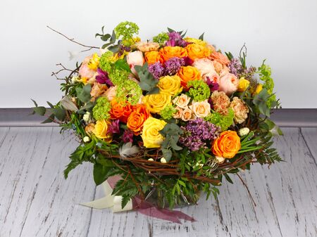 Flower arrangement with roses, lilac and alstroemeria on light wooden floor