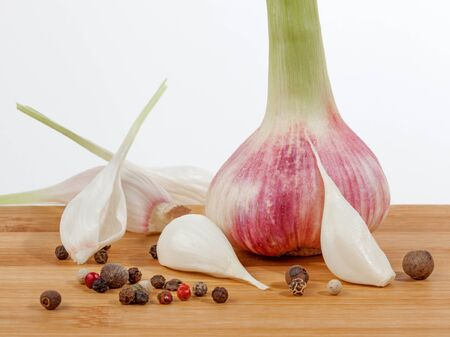 Close up fresh young garlic bulb and peppercorns mixture on wooden  cutting board