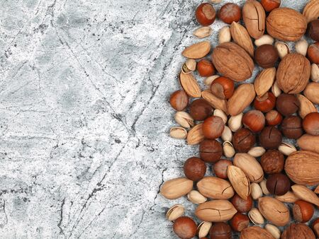 Mix of raw inshell nuts on gray stone background. Top view with copy space