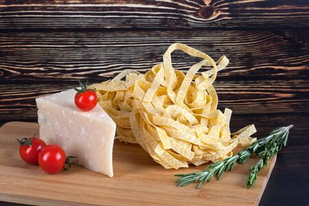 Dry Italian pasta fettuccini with tomatoes, cheese and rosemary on dark wooden background. With copy space