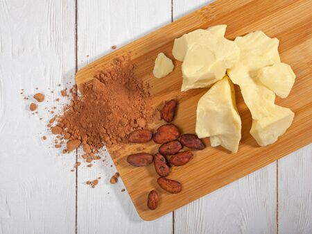 Pieces of natural cocoa butter, cocoa powder and cocoa beans on 