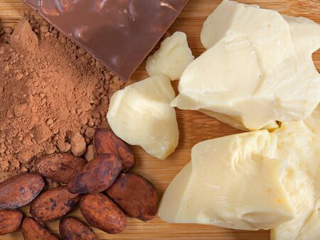 Pieces of natural cocoa butter, bar of milk chocolate, cocoa powder 