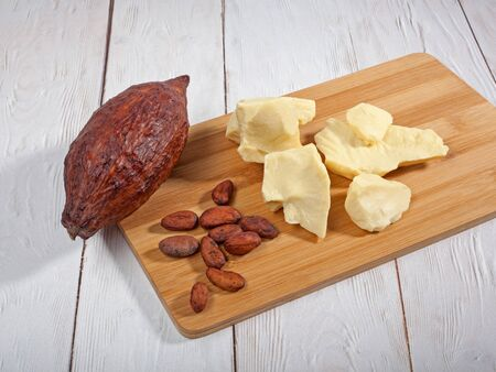 Pieces of natural cocoa butter, cocoa pod and cocoa beans on wooden 