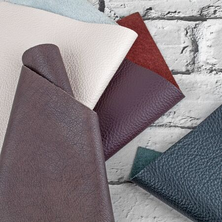 Different colors natural leather textures samples on grey brick 