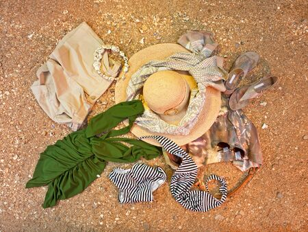 Women's clothing lying down on sandy beach. Top view