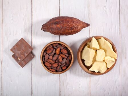 Broken bar of milk chocolate, cocoa pod, cocoa butter and cocoa 