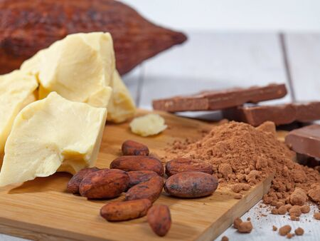 Pieces of natural cocoa butter, bar of milk chocolate, cocoa powder, cocoa pod and cocoa beans on wooden cutting board