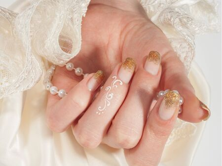 Closeup shot of woman`s hand with golden manicure on white background