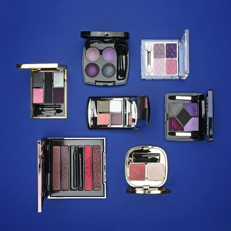 Cosmetic sets with eye shadows and brushes in black plastic cases with mirror on blue background Zdjęcie Seryjne