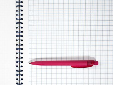 Red pen on white notepad in the cage with blue spiral wire binding. Isolated on white background