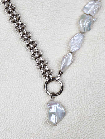 Luxury elegant baroque pearl necklace with pendant on white leather background. Close-up shot