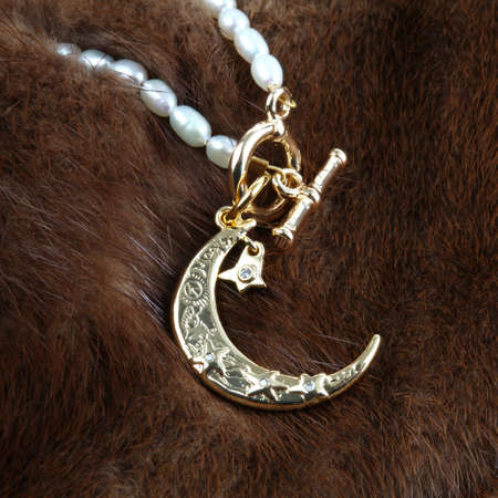 Golden crescent moon pendant with pearl necklace on brown fur background