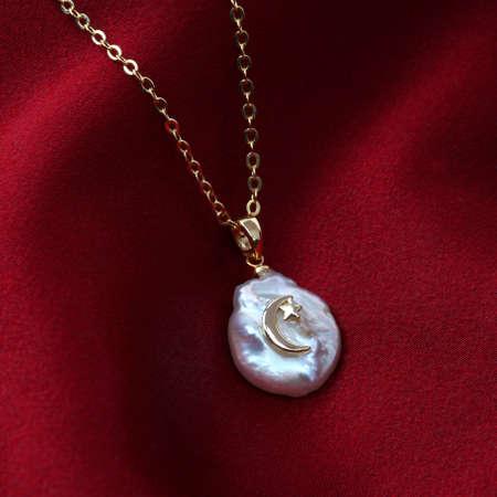 Golden crescent moon baroque pearl pendant with gold chain on red silk texture satin velvet material Standard-Bild