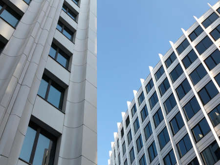 Modern buildings from low angle view against blue sky. Commercial office buildings exterior