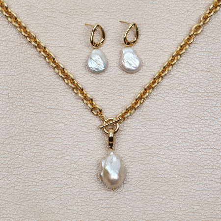 Gold necklace with white baroque pearl pendant and earrings on beige leather background. Top view