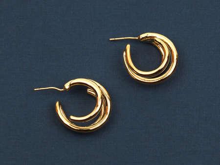 Modern gold women`s earrings on dark blue textured background