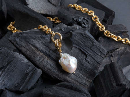 Golden chain with white baroque pearl pendant on black coal background. Close-up shot